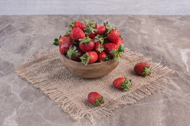 Tazón de fresas sobre un trozo de tela sobre la superficie de mármol