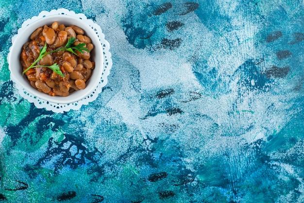 Un tazón de frijoles horneados en una montaña rusa, sobre el fondo azul.