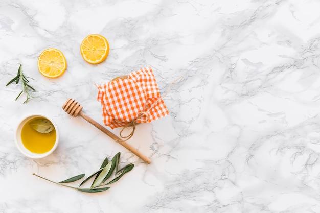 Tazón de fuente del aceite de oliva, rebanada del limón, y tarro en el fondo blanco