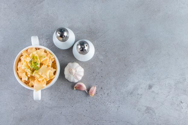 Tazón de fuente blanco de deliciosos macarrones con ajo y sal sobre fondo de piedra.
