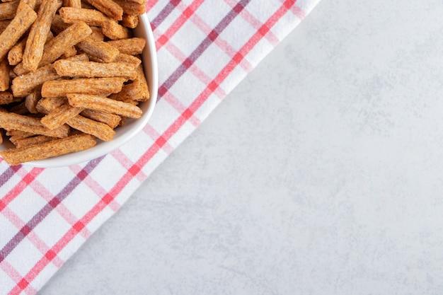 Tazón de fuente blanco de galletas crujientes de palo sobre fondo de piedra.