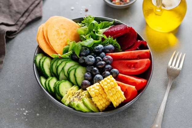 Tazón de fuente de buda vegano con verduras y frutas servido en un tazón sobre fondo gris. de cerca