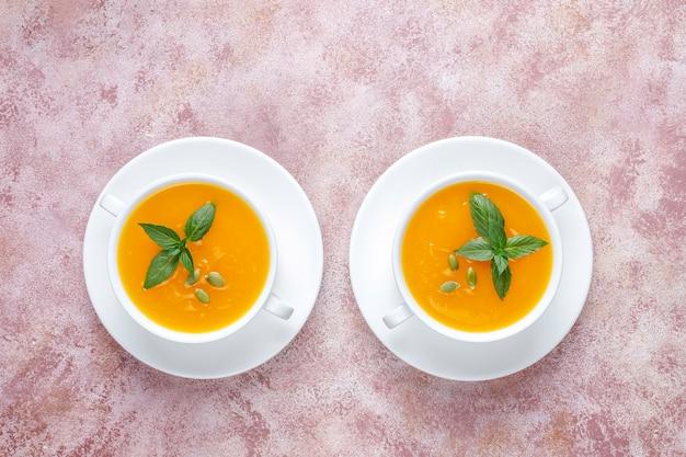 Tazón de fuente de deliciosa sopa de calabaza con semillas.