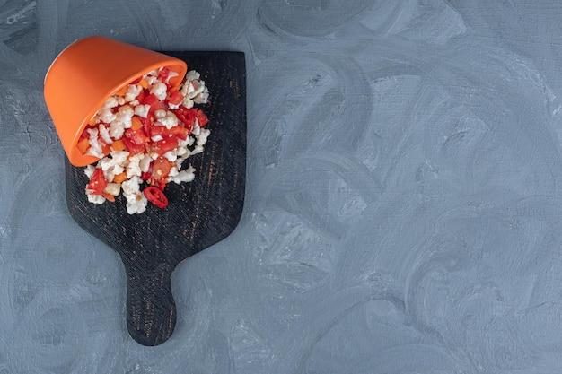 Tazón de fuente de ensalada de coliflor y pimiento derramado sobre una tabla de madera sobre fondo de mármol.