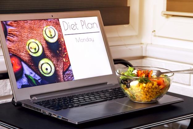 Tazón de fuente de ensalada vegetal cerca de la computadora portátil en la mesa. en la pantalla - planeando una dieta para bajar de peso desde el lunes