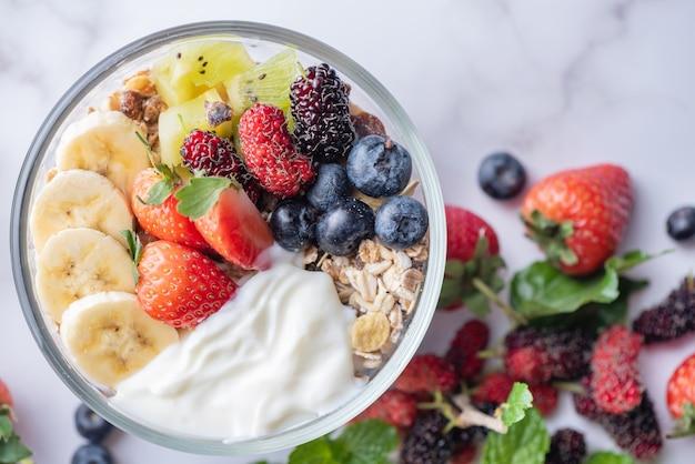 Tazón de fuente de granola de avena con yogur, arándanos frescos, moras, fresas, kiwi, plátano, menta y nueces para un desayuno saludable, vista superior, espacio de copia, endecha plana. concepto de comida vegetariana.