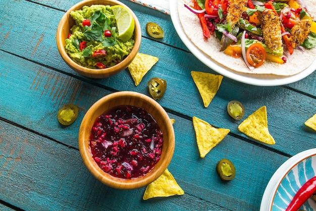 Tazón de fuente de guacamole con ensalada vegana en pita y patatas fritas en una mesa de madera azul bajo las luces
