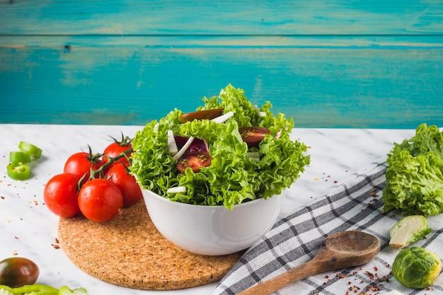 Tazón de fuente de ingrediente de ensalada verde en montaña de madera