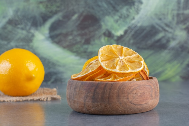 Tazón de fuente de limones en rodajas y limón entero sobre fondo de piedra.