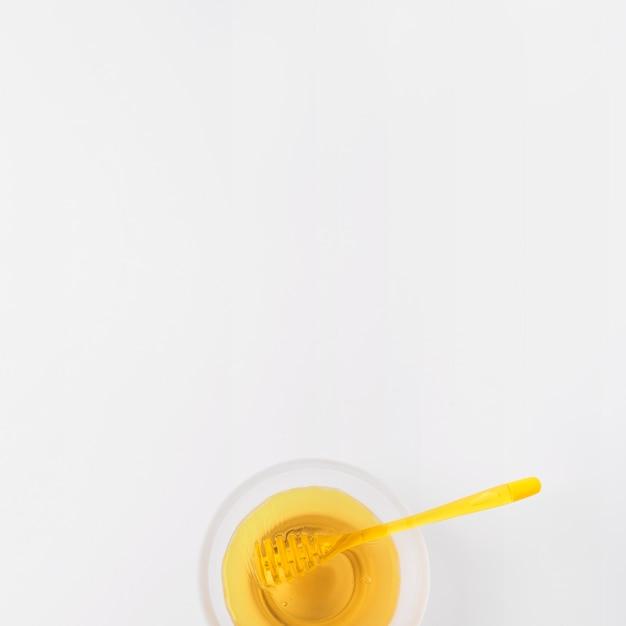 Tazón de fuente de miel con cucharón en superficie blanca
