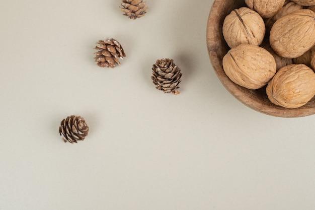 Tazón de fuente de nueces y piñas sobre superficie beige