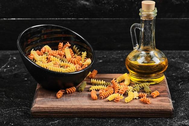 Tazón de fuente de pasta fusilli colorida y botella de aceite en la mesa oscura.