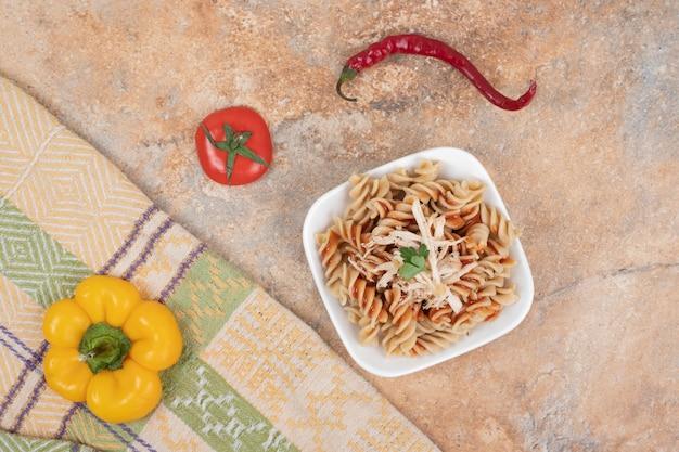Tazón de fuente de pasta fusilli y verduras frescas sobre mantel