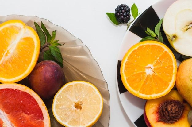 Tazón de fuente y placas de frutas coloridas aisladas sobre fondo blanco