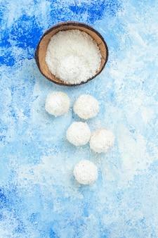 Tazón de fuente de polvo de coco de vista superior y bolas de coco sobre fondo blanco azul