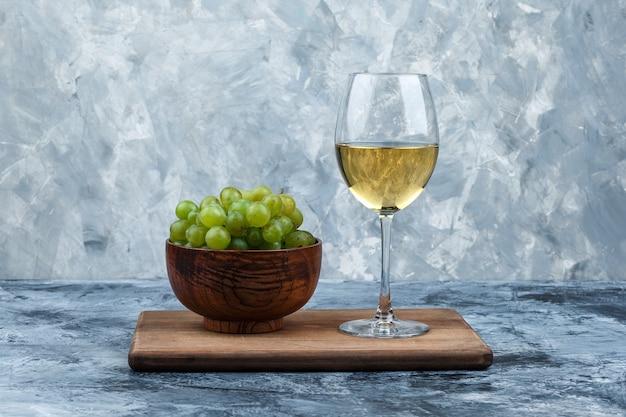 Tazón de fuente de primer plano de uvas blancas, vaso de whisky en la tabla de cortar sobre fondo de mármol azul claro y oscuro. horizontal
