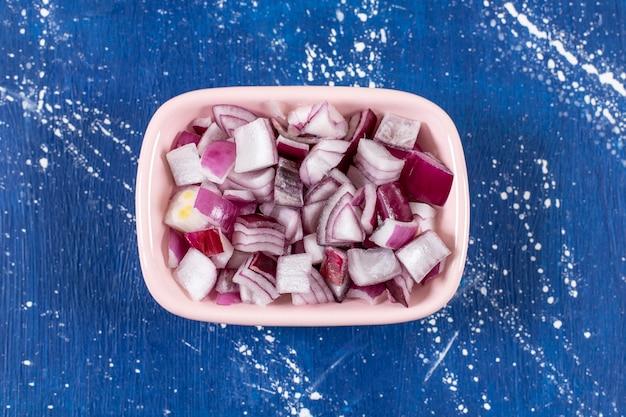 Tazón de fuente rosa de cebollas moradas en rodajas sobre la superficie de mármol