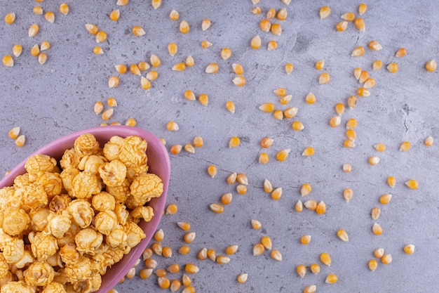 Tazón de fuente rosa de palomitas de maíz saladas en la superficie de la piedra