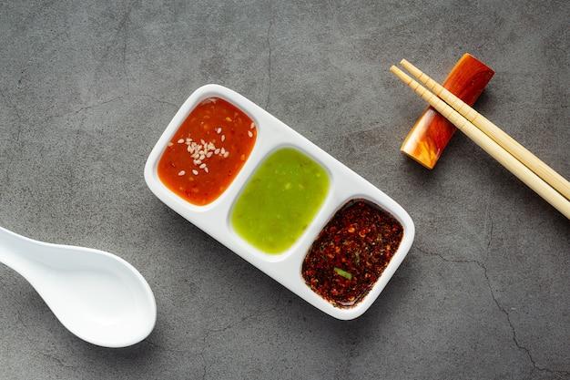 Tazón de fuente de salsa de inmersión de olla caliente shabu lugar en el piso oscuro