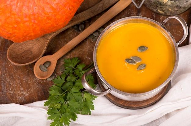 Tazón de fuente de sopa de calabaza sobre fondo de madera rústica.