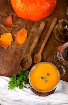 Tazón de fuente de sopa de calabaza en la superficie de madera rústica.