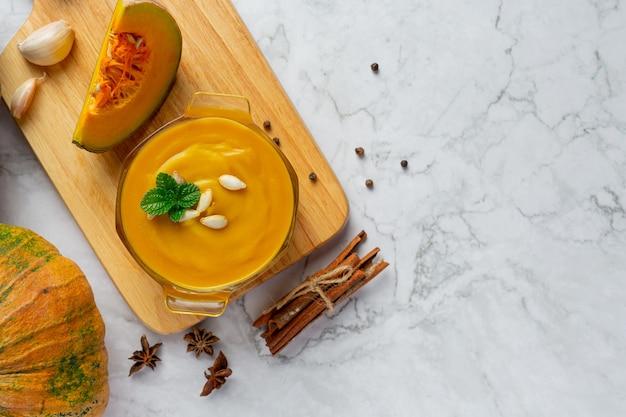 Tazón de fuente de sopa de calabaza en la tabla de cortar de madera