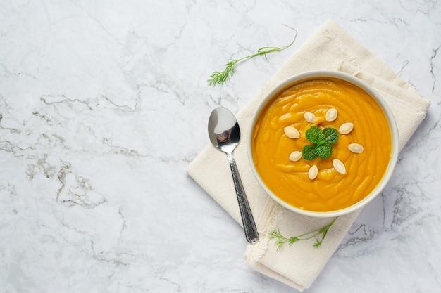 Tazón de fuente de sopa de calabaza en tela blanca