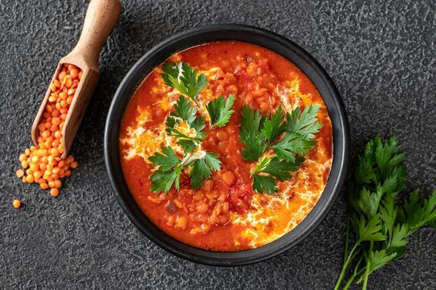 Tazón de fuente de sopa de tomate y coco de lentejas plano