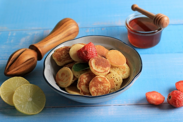 Tazón de fuente con tiny pancake cereal con fresas, limón y hojas de menta sobre un fondo azul de cerca. comida de moda. mini tortitas de cereales. orientación horizontal