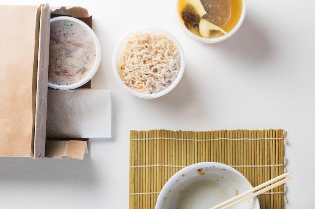 Tazón de fuente vacío cerca de comida asiática para llevar