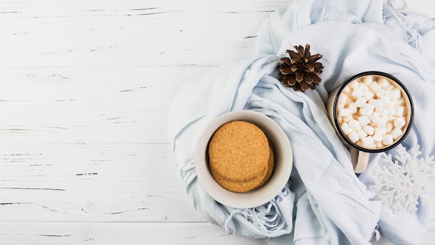 Tazón con galletas cerca de la taza con malvaviscos y enganchar en la bufanda