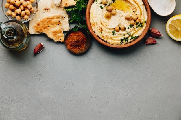 Tazón grande de hummus casero adornado con garbanzos, pimiento rojo, perejil y aceite de oliva.