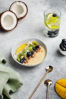 Tazón de granola con batido de mango sobre leche de coco con mango, kivi, coco, arándano. agua detox