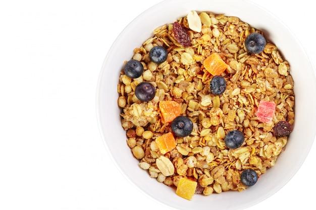 Tazón de granola casera con trozos de fruta aislados en blanco