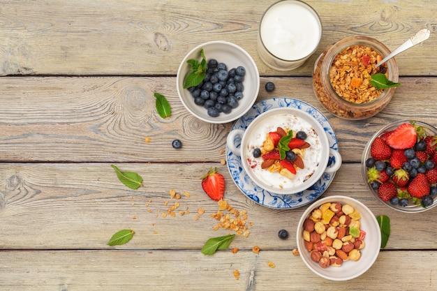 Tazón de granola casera con yogur y bayas frescas en madera
