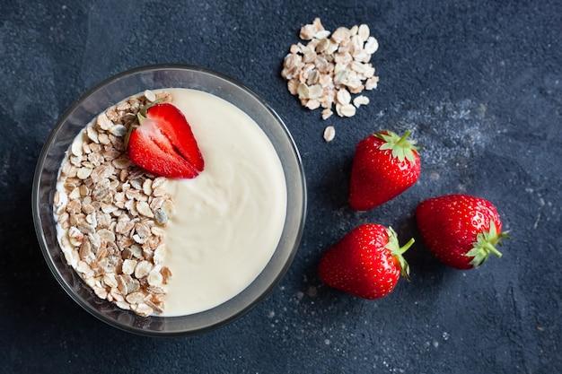 Tazón de granola casera con yogur y fresas frescas sobre un fondo gris