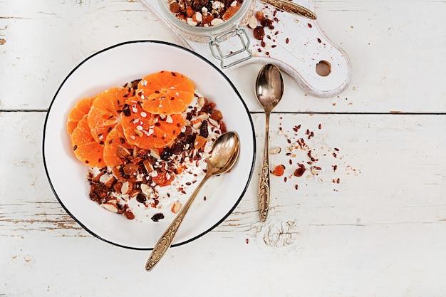Tazón de granola casera con yogurt y mandarina en mesa de madera blanca