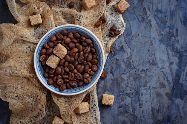Tazón de granos de café y azúcar de caña marrón. enfoque selectivo