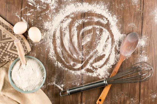 Tazón de harina con huevos y cuchara de madera