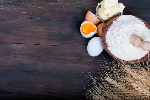 Tazón con harina huevos espigas de trigo y mantequilla en concepto de comida y bebida de tablero de madera vintage