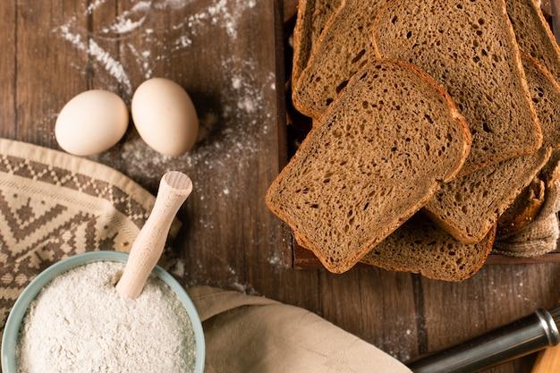 Tazón de harina con huevos y rebanadas de pan