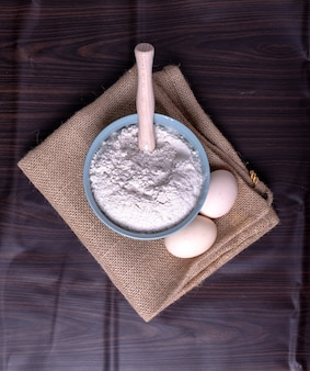 Un tazón de harina con huevos sobre mantel