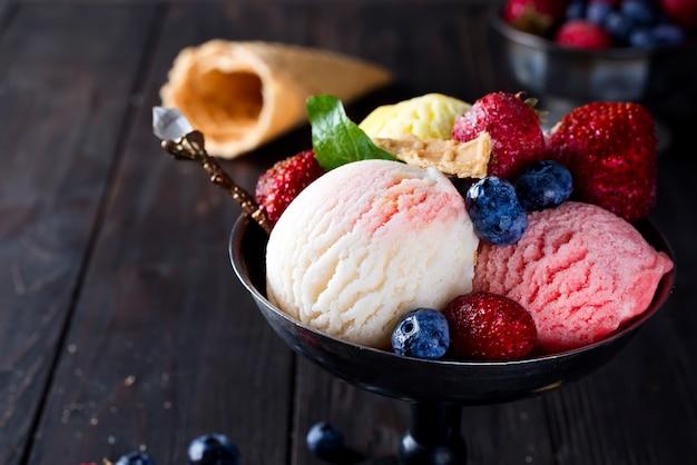 Tazón con helado con tres bolas diferentes de blanco, amarillo, colores rojos y cono de waffle