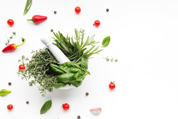 Tazón con hierbas rodeado de vegetales