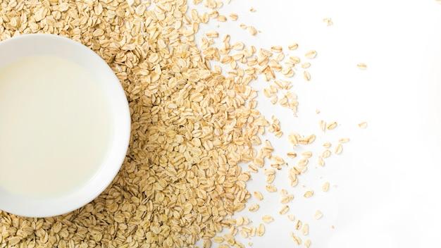 Tazón de leche saludable sobre las copos de avena seca sobre el fondo blanco