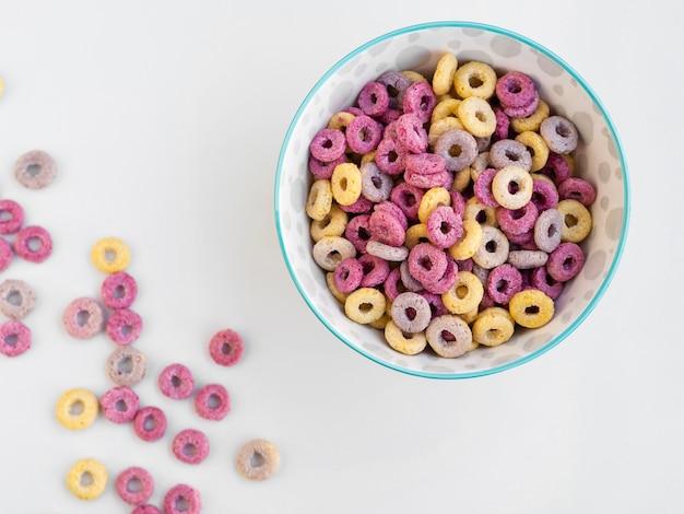 Tazón lleno de bucles de cereales de frutas sobre fondo blanco.