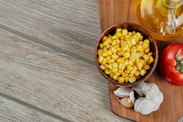 Un tazón de maíz dulce hervido, aceite y verduras sobre una tabla de madera.