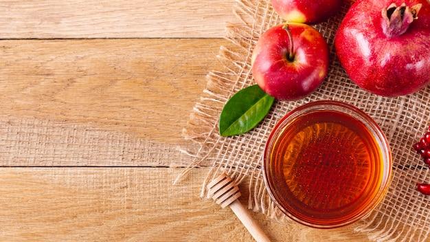 Tazón de miel con cucharón y frutas con espacio de copia