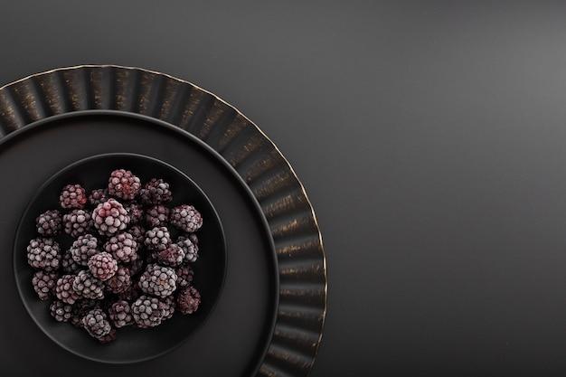 Tazón de moras en un plato oscuro