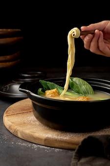 Tazón negro con sopa de fideos en un plato de madera